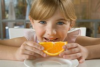 Young girl holding orange slice