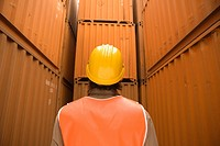 Rear view of a male dock worker wearing a hardhat