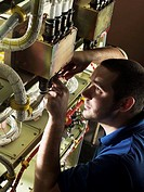 Aircraft construction. Aviation electronics technician attaching wiring upper left to the communications module of a military helicopter.