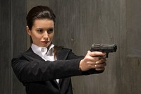 Young businesswoman holding gun