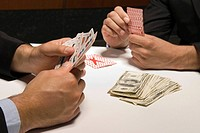 Close_up of businessmen playing cards for money