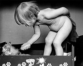 Side view of a nude girl feeding doll