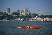 Young woman sea kayaking in the St Lawrence River near Quebec City, Quebec, Canada.