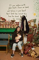 A sad young mom feeds her baby next to a christmas tree in a shelter for low income and homeless children and families at a shelter in Barstow, CA. No...