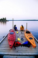 Kayakers relaxing on Nutimik Lake campground boat dock, Whiteshell Provincial Park, Manitoba, Canada.