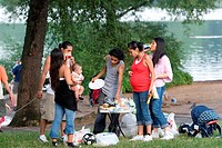 Young Hispanic family and friends have a picnic in Prospect Park, Brooklyn, New York.