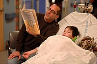 To help pass the time, a father reads to his sick child while waiting to be seen by a doctor.