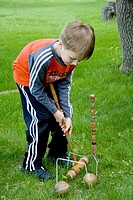 Boy age 7 returning wooden ball through double croquet wickets with a long-handled mallet  Clitherall Minnesota USA