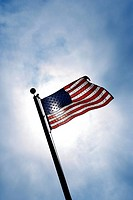 American flag blowing in breeze against blue sky.