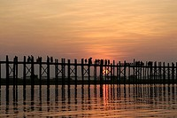 Silhouette of group of people walking on bridge across river at dusk, U Bein Bridge, Amarapura, Myanmar