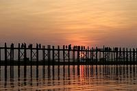 Silhouette of group of people walking on bridge across river at dusk, U Bein Bridge, Amarapura, Myanmar