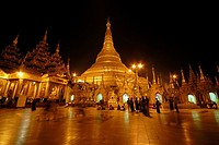 Group of people at Buddhist temple lit up during dusk, Shwedagon Pagoda, Yangon, Myanmar