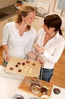 High angle view of woman and her daughter preparing food in kitchen