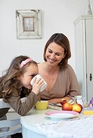 Woman looking at her daughter drinking milk