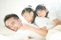 Family relaxing in bed room