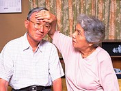 Senior adult woman checking husband's temperature, Front View