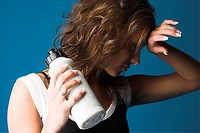 Female model holding a drinking bottle and looking tired after a fitness session