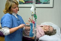 Clinic nurse removing cast of a senior citizen