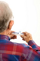 Over the shoulder view of Caucasian elderly man holding seven-day pill box (thumbnail)
