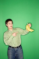 Portrait of Caucasian teen boy holding and pointing at bananas standing against green background