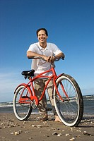 Caucasian mid_adult man posing with red bicycle on beach