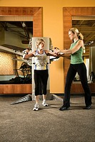 Adult Caucasian female helping mature adult Caucasian female use exercise equipment at gym