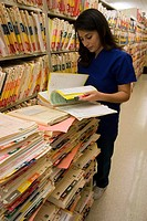 Portrait of young adult nurse filing