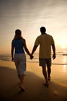 Caucasian mid_adult couple walking holding hands on beach at sunset.