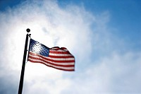 American flag blowing in breeze against blue sky