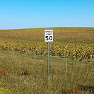 Speed limit sign in front of rural field of crops