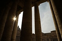 Sun peeking through Doric columns in Saint Peter's Square in Vatican City, Italy