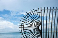 Decorative wrought iron fence at the edge of the sea