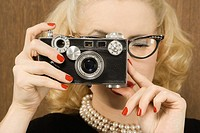 Mid_adult Caucasian female in vintage outfit holding a vintage film camera up to her face.