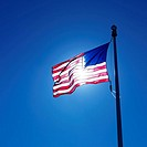 American flag on flagpole waving against blue sky with sun shining through from behind