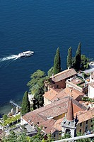 Boat in water offshore Lago di Como with red tiled rooftops, church and cypress trees from above Italy