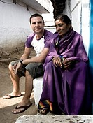 Western man sits with Indian village woman both wearing purple