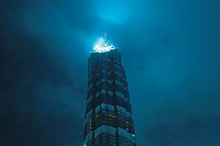the Jin Mao Tower Under a Cloudy Sky, the Top Shining in a Blue Color, Low Angle View, Shanghai, China