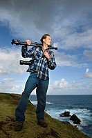 Caucasian mid_adult man standing with camera and tripod over his shoulder on cliff overlooking ocean in Maui, Hawaii.