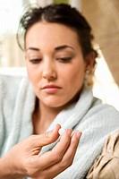 Caucasian/Hispanic young woman in bathrobe holding pill in hand.