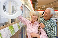 Mature couple looking at washing machine in shop, smiling, portrait of woman
