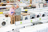 Mature couple shopping for appliances, looking at brochure