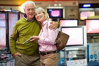Mature couple arm in arm, shopping for television, smiling, portrait (thumbnail)