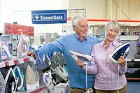 Mature couple shopping for iron, smiling
