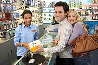 Young couple with saleswoman buying camera, smiling, portrait, side view