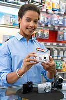 Young saleswoman with camera, smiling, portrait, low angle view