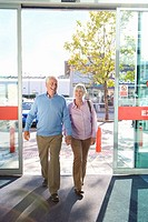 Mature couple walking hand in hand through glass doors, smiling, portrait