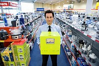 Young man with box in electronics aisle, smiling, porttrait