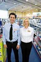 Young salesman and woman in electronics aisle, smiling, porttrait