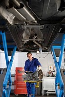 Mechanic with part by elevated car, portrait, low angle view