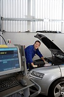 Mechanic working on car by computer, smiling, portrait